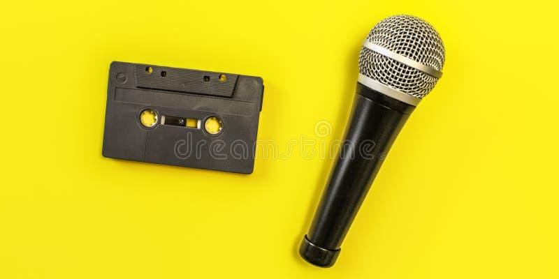 Tabletop sikt - ljudkassett och mikrofon på gult bräde royaltyfri foto