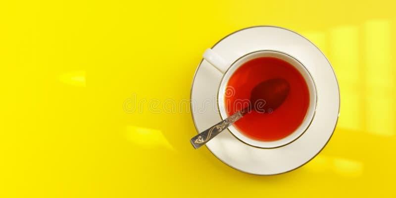 Tabletop sikt, morgonsolsken till den vita porslinkoppen med varmt te, silversked in, på det gula brädet - brett foto arkivfoton