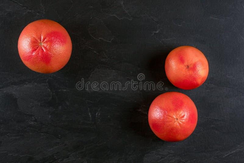 Tabletop sikt - tre hela rosa grapefrukter på svart kritiserar som brädet, utrymme för text lämnade ner arkivbilder