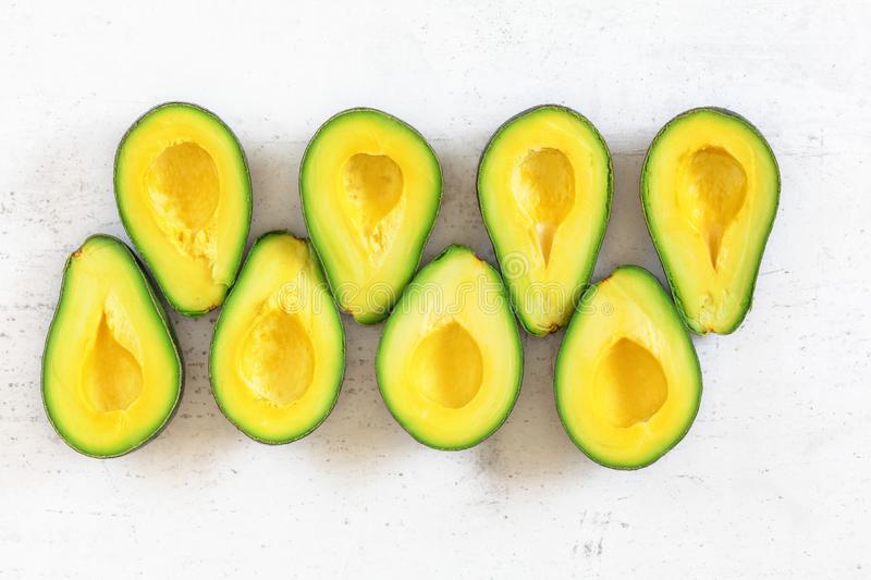 Tabletop view - avocado sliced to halves, arranged in two rows on white working board. royalty free stock photo