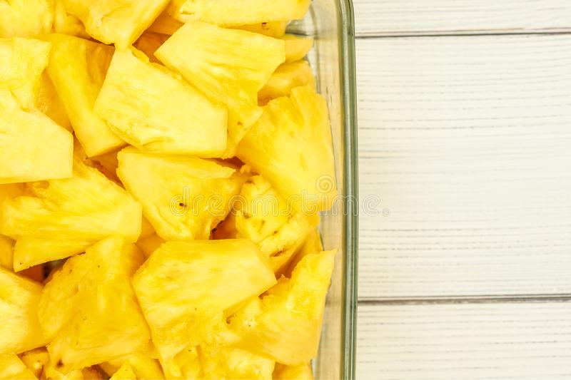 Tabletop view - close up of ripe pineapple cut into pieces, in g stock photo