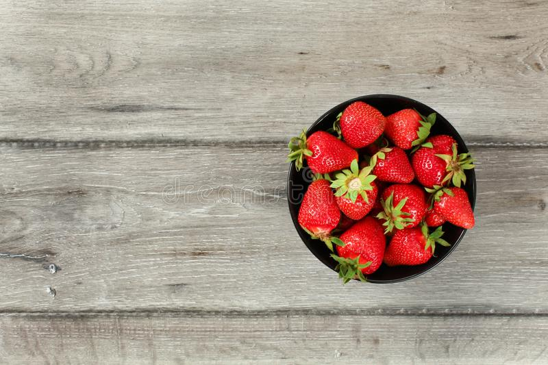 Tabletop view, small black ceramic bowl with strawberries, gray wood desk under. Space for text on left side royalty free stock photography