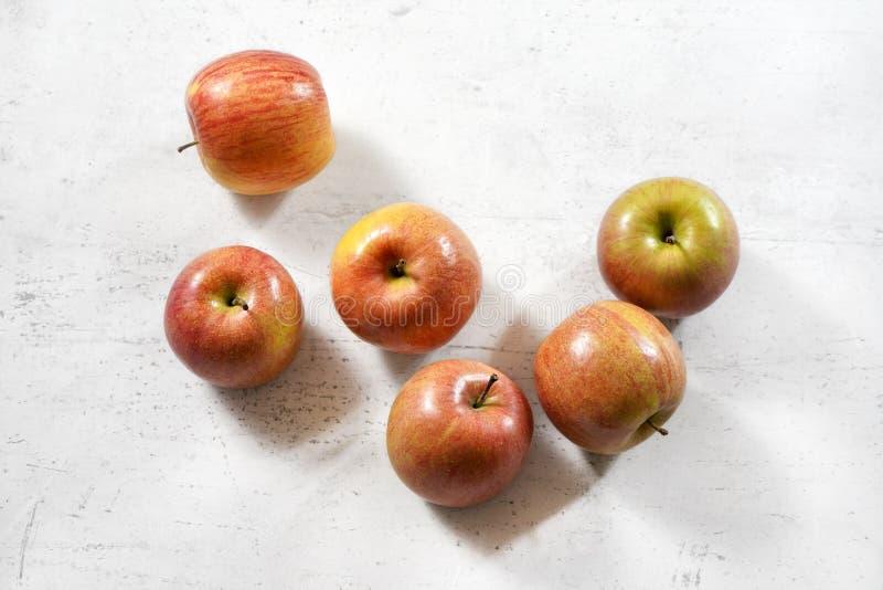 Tabletop widoku - czerwona, żółta jabłka kiku rozmaitość na białej działanie desce/ zdjęcia royalty free