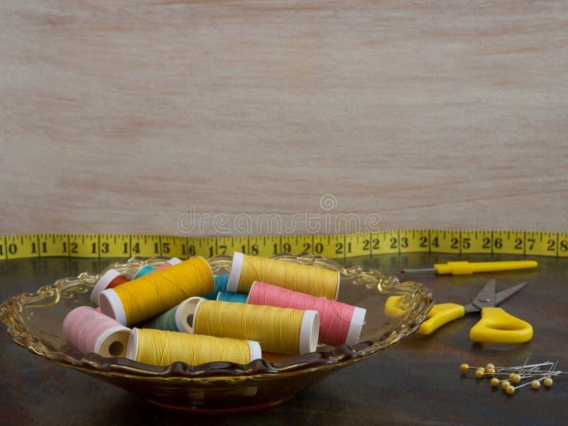 Tabletop z szwalnymi materiałami w kolorze żółtym Copyspace na lekkim tle zdjęcie stock