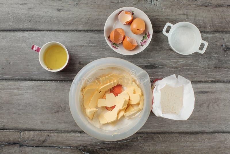 Tabletopsikt - plast- bunke med mjöl, äggulor och smör, M royaltyfri bild