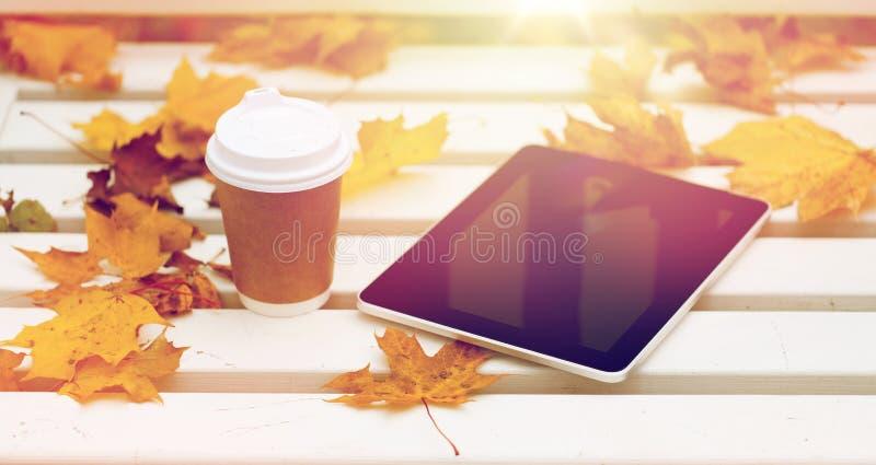 Tabletpc en koffiekop op bank in de herfstpark royalty-vrije stock fotografie