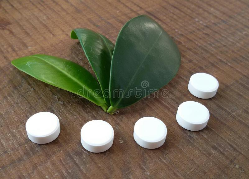 White tablets and green leaves over wooden background symbolizing homeopathy. Tablets over wooden background. Green leaves. Homeopathy stock images
