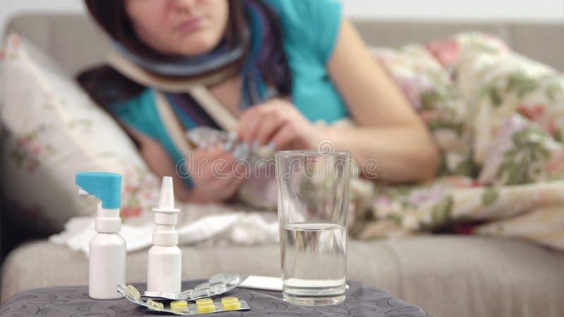 Tablets, Spray und Wasser auf dem Stuhl und der jungen kranken Frau nimmt eine Pille im Bett auf dem Hintergrund ein lizenzfreie stockfotografie