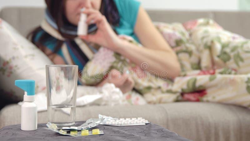 Tablets, Spray und Wasser auf dem Stuhl und junge kranke Mädchennehmenheilung für Rotz auf dem Hintergrund stockbilder