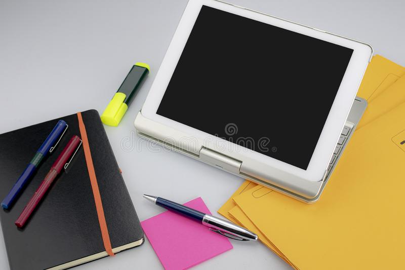 Tablette avec clavier, marqueur fluorescent, marqueur rouge et bleu, stylet, notes collantes et bloc-notes sur fond blanc images libres de droits