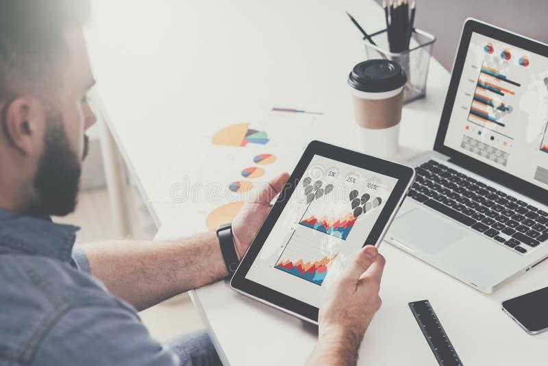 Tablette avec des graphiques, des diagrammes et des diagrammes sur l'écran dans des mains du jeune homme d'affaires barbu s'assey photo stock
