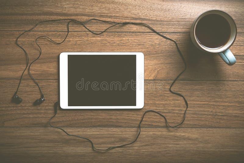 Tablette avec du café sur le bois avec des écouteurs photos stock