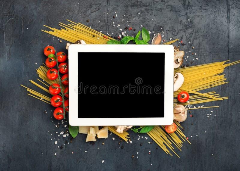 Tablette avec l'espace de copie et ingrédients pour faire cuire les pâtes italiennes image stock