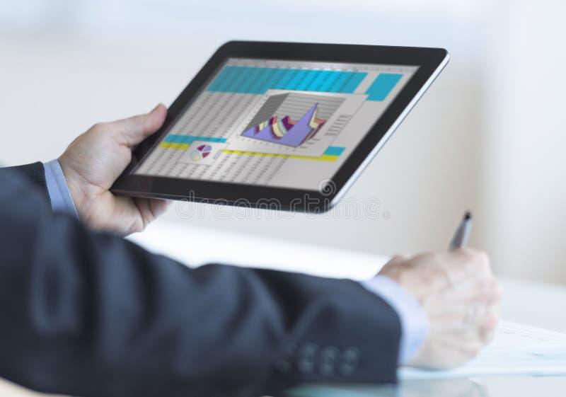 Tablette d'Analyzing Graph On Digital d'homme d'affaires images libres de droits