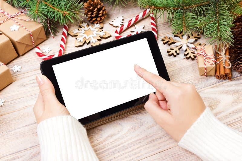 Tablette dans des mains de fille la tablette avec le boîte-cadeau, la sucrerie de Noël et le sapin rouges s'embranche L'espace li photographie stock
