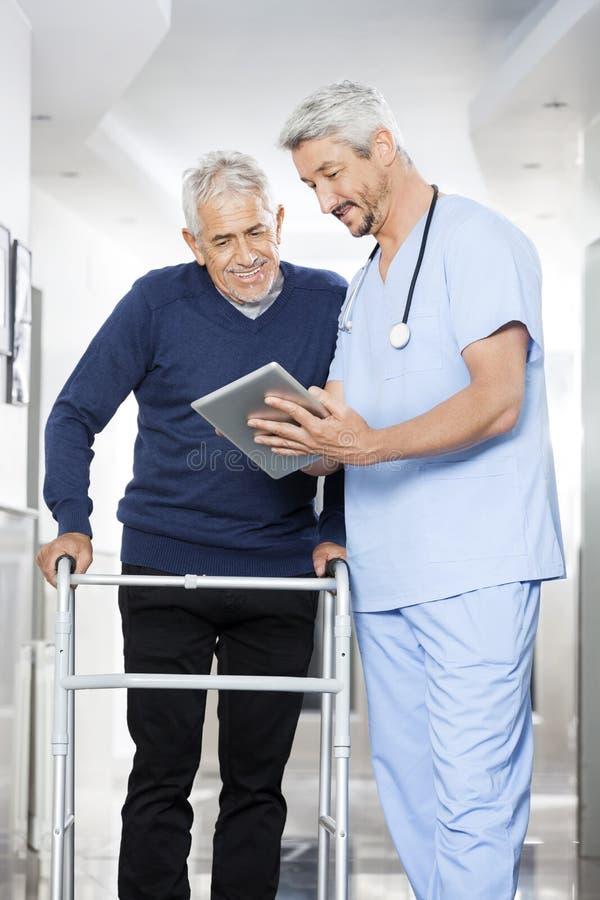 Tablette de Showing Reports On Digital de physiothérapeute à l'homme supérieur photo libre de droits