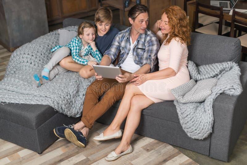 Tablette de sourire heureuse d'utilisation de famille se reposant sur le divan dans la vue d'angle supérieur de salon, parents pa photographie stock