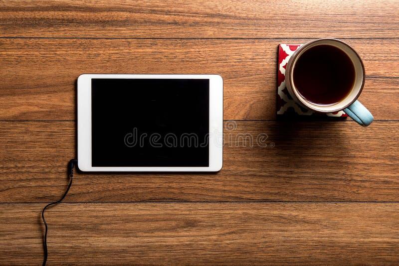 Tablette et café sur le bois avec le fil photographie stock