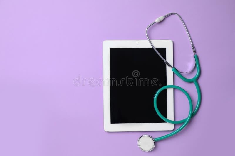 Tablette et stéthoscope sur le fond lilas, vue supérieure Soin de gynécologie photo stock