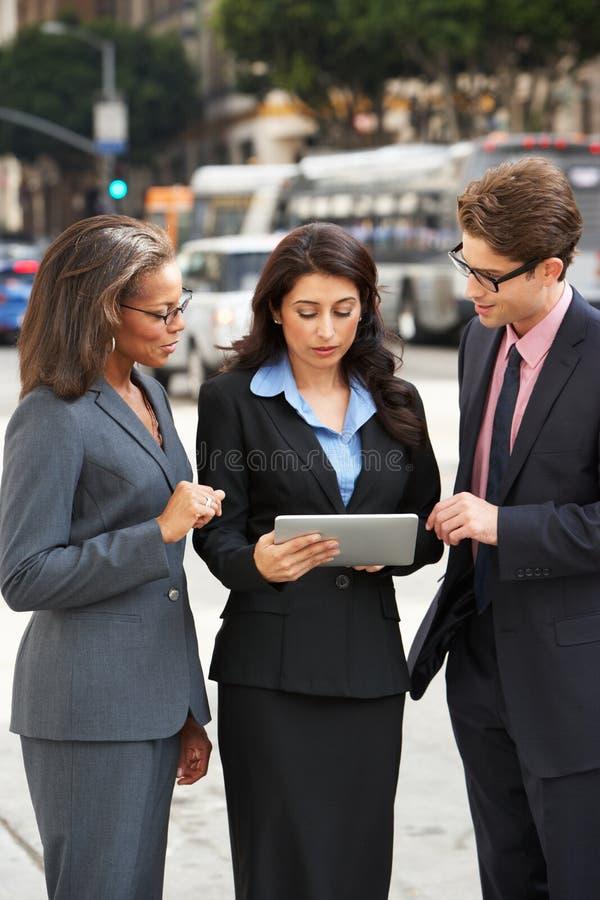 Tablette Geschäftsmann-And Businesswomen Usings Digital draußen stockfotografie