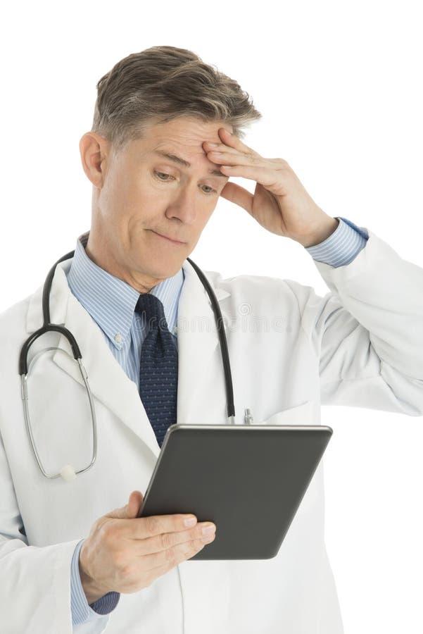 Tablette masculine confuse de docteur Looking At Digital photos libres de droits