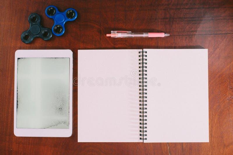 Tablette, stylo, fileur de main, carnet sur le fond en bois de table images stock