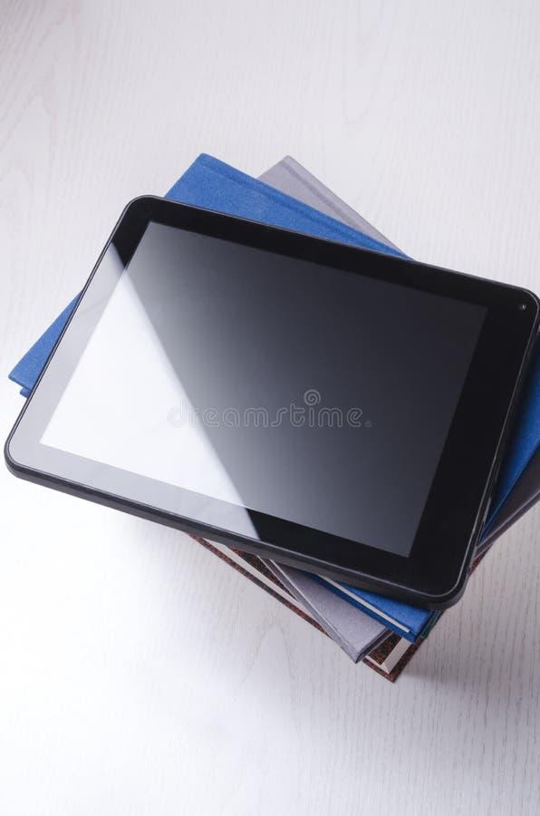 Tablette sur des livres Concept d'apprentissage en ligne, de formation de distance et de lecture en ligne image libre de droits