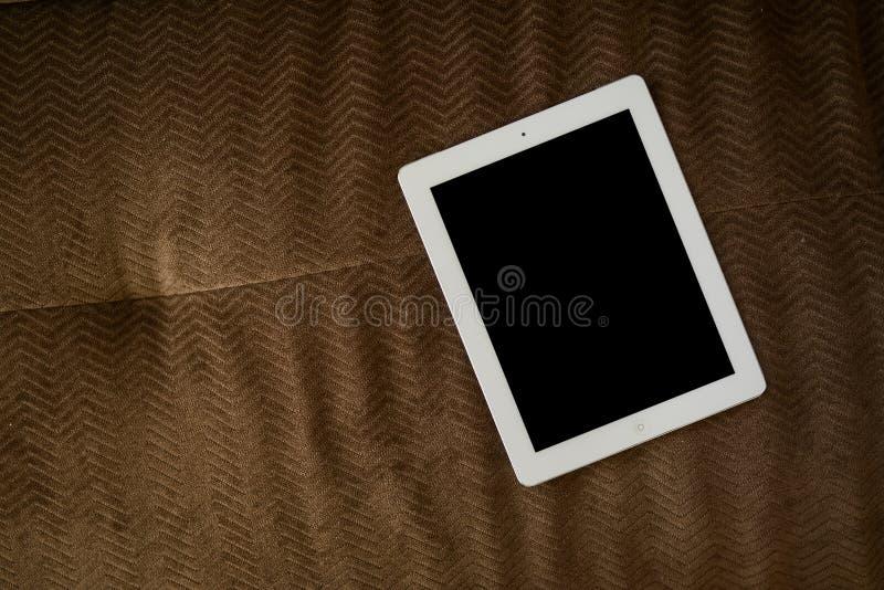 Tablette sur le sofa brun image libre de droits