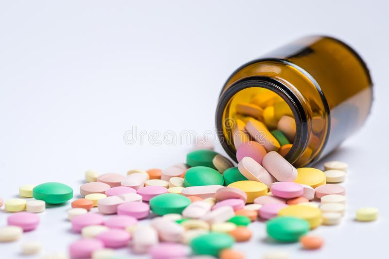Tabletten in de glasfles op een witte achtergrond stock afbeeldingen