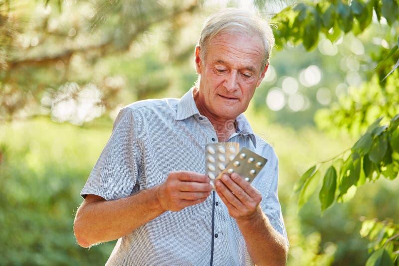 Tabletten des älteren Mannes auf seiner Hand lizenzfreies stockbild