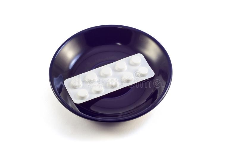 Tabletten op een donkerblauwe plaat stock afbeelding