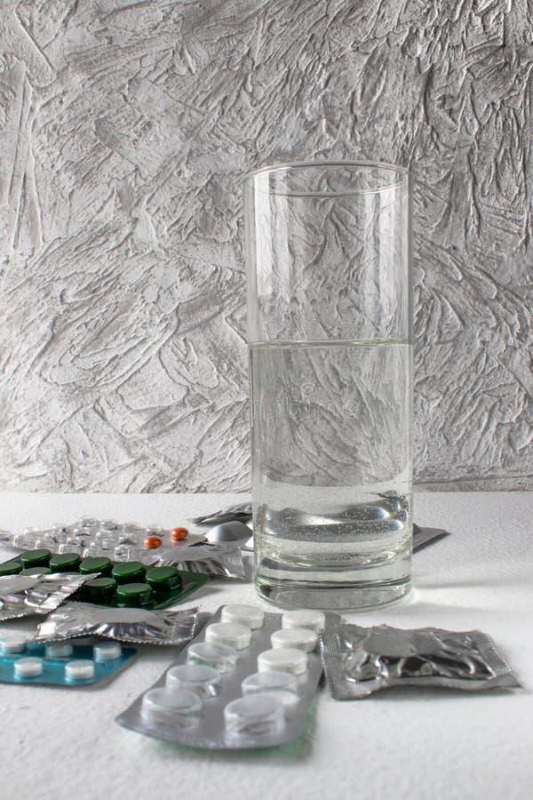 Tabletten in pakken op een witte achtergrond dichtbij een glas water Pillen stock foto