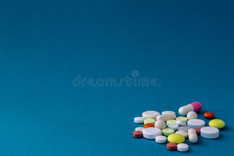 Tabletten van verschillende kleuren en vormen op blauwe grijze achtergrond stock fotografie