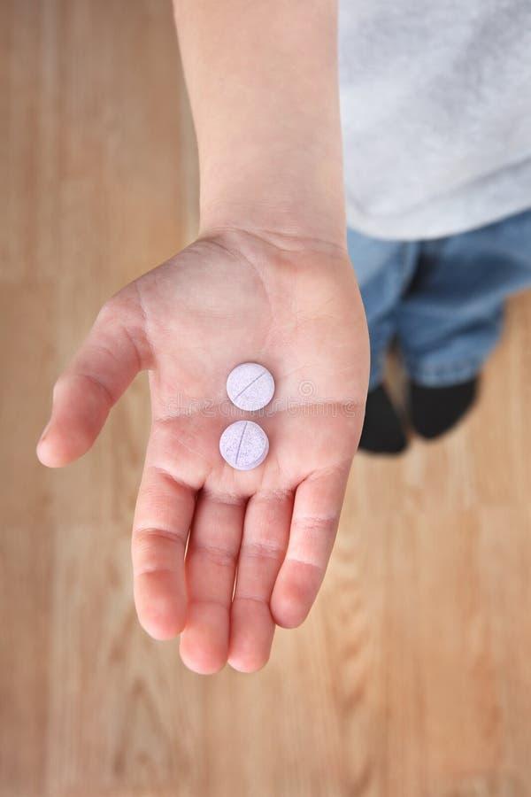 Tablettes de médecine de fixation de la main de l'enfant photos libres de droits