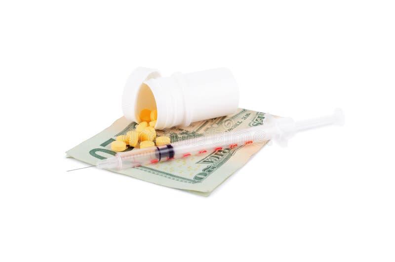 Tablettes et seringue sur un billet d'un dollar américain d'isolement sur le blanc images stock