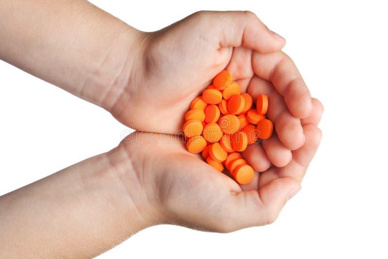 Tablettes oranges chez les paumes des enfants image libre de droits