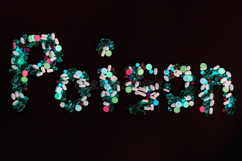 Tablettes, pilules et capsules, qui créent le poison de mot, sur le fond noir images stock