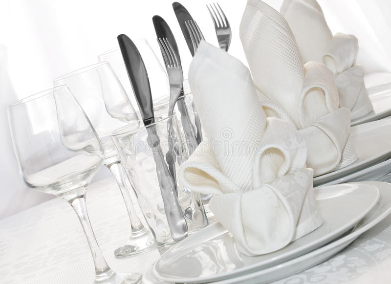 Tableware. Decoratively folded napkins with glasses, glasses and cutlery royalty free stock image