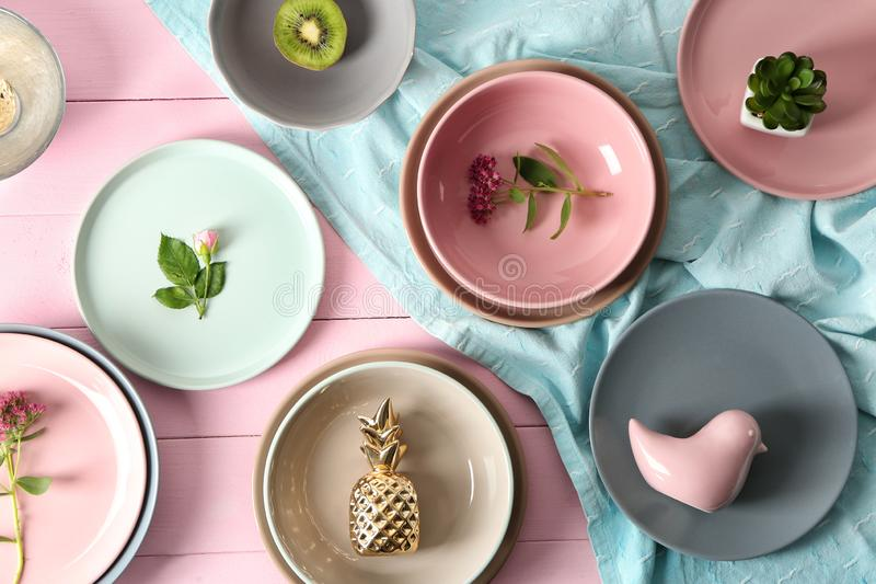 Tableware, flowers and decorations on pink wooden background stock images
