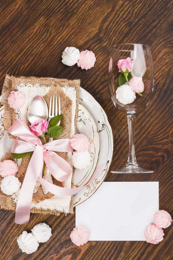 Tableware and silverware with puffy light pink roses. On the wooden background, top view stock image