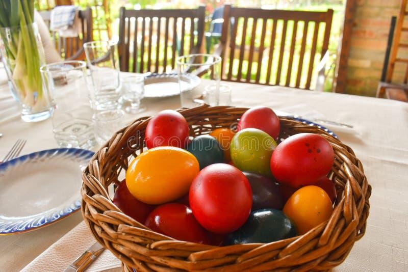 Tablewear de Pascua al aire libre debajo de la pérgola con los huevos coloridos en un día soleado imagen de archivo