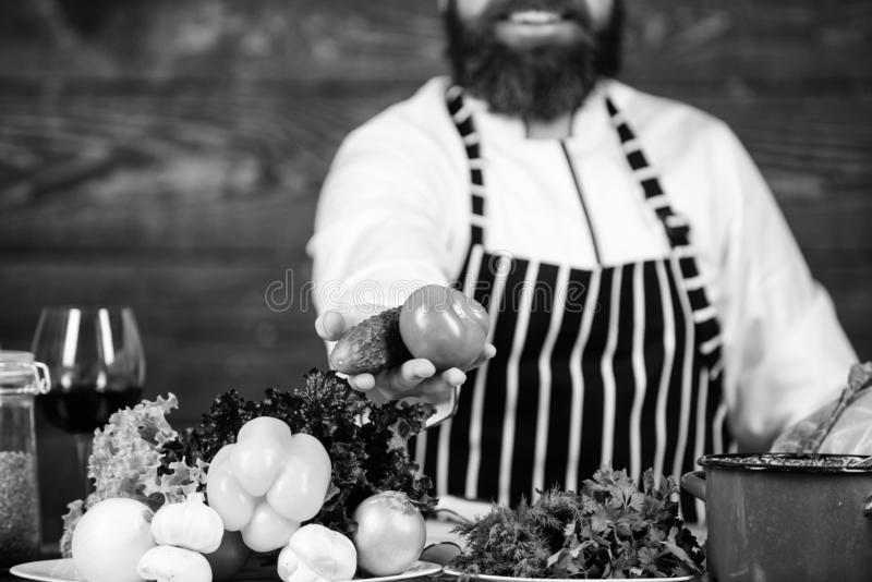 Tablier barbu d'usage de hippie d'homme faisant cuire la nourriture saine Mode de vie v?g?tarien Le chef pr?parent le fond en boi photos stock