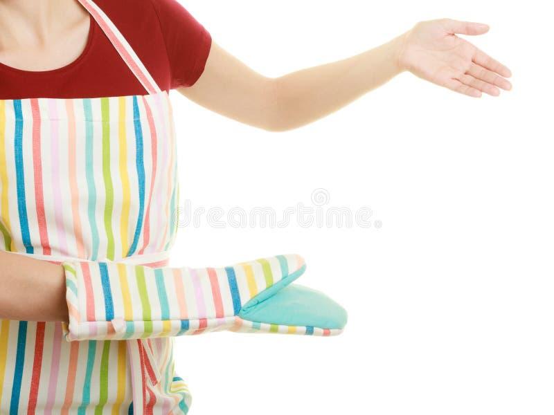 Tablier de cuisine de femme au foyer faisant le geste bienvenu de invitation images libres de droits