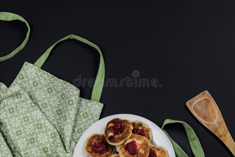Tablier vert, spatule en bois et plat avec des crêpes de fromage de coton sur un fond foncé avec l'espace de copie image libre de droits