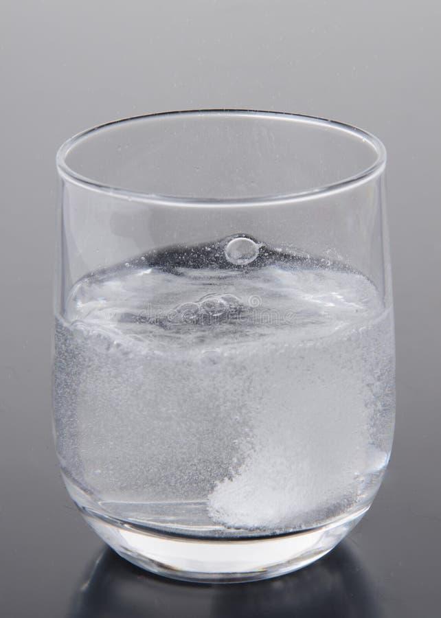 Tablilla efervescente en un vidrio de agua imagen de archivo