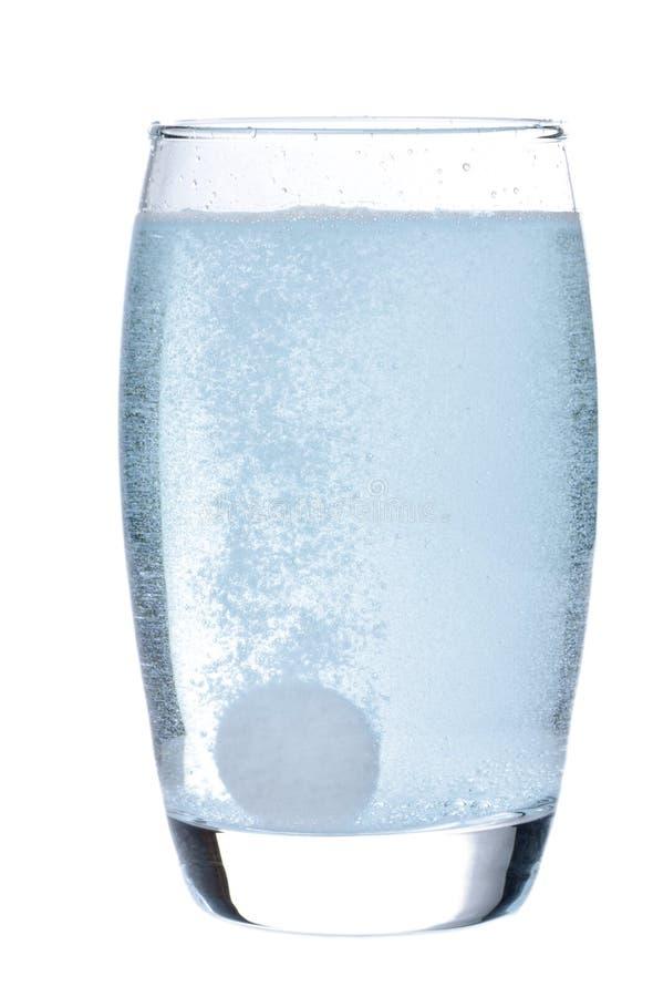 Tablilla efervescente en vidrio con agua fotos de archivo