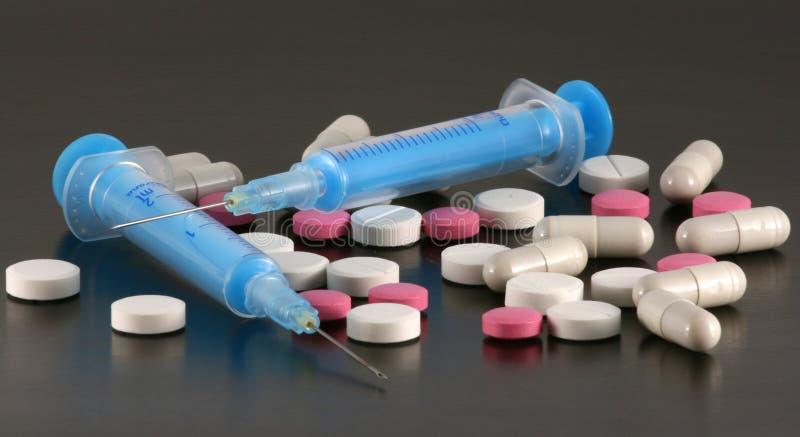 Tablillas, píldoras y jeringuillas foto de archivo