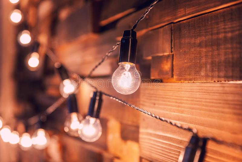 Tablones de madera con el fondo de las l?mparas Sitio interior adornado con las luces del oro imagen de archivo