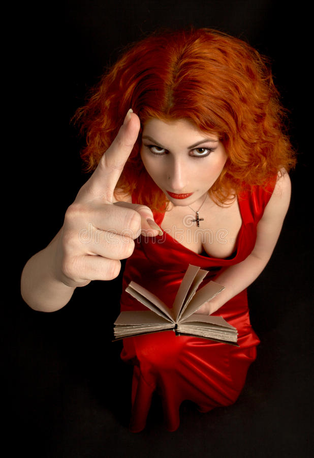 Taboo. Redhead religious lady with a book showing finger (focus on hand royalty free stock photo