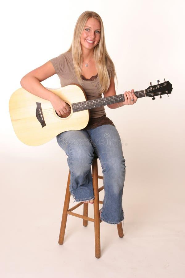 Tabouret de l'adolescence blond de guitare photos stock